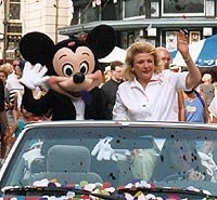 Barbara Taylor Bradford and Mickey Mouse wave to the crowd at the end of the parade route from their confetti covered car in Walt Disney World, Orlando, Florida